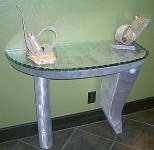 foyer table in abstract design and brushed aluminum and contemporary glass top in aluminum table